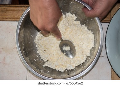 Stirring cottage cheese and egg in a metal bowl. Top view image