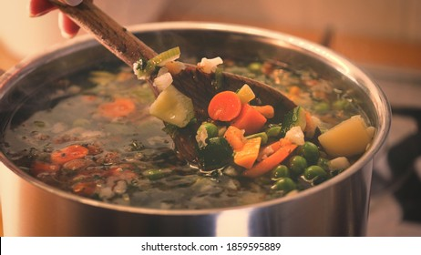 stirring a pot of vegetable soup. Minestrone soup boiling in the pot. Vegetarian healthy meal for dinner. Ready vegetable meal for lunch, hot and cozy soup for dinner at home
