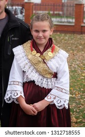 STITAR, CROATIA - OCTOBER 28, 2018: Girl dressed in folk costumes go to the church at the Mass on Thanksgiving day in Stitar, Croatia