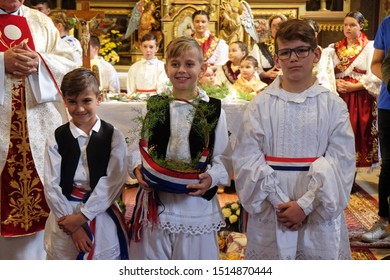 STITAR, CROATIA - OCTOBER 28, 2018: Children dressed in traditional regional folk costumes in the church at the Mass on Thanksgiving day in Stitar, Croatia