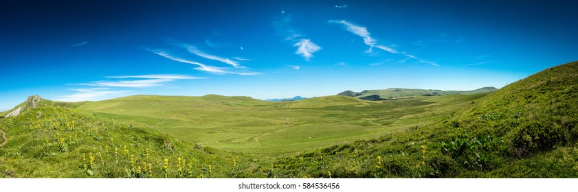 Stitched panorama of the lush green hills in the Auvergne countryside in France under a sunny blue sky in a travel and vacation concept
