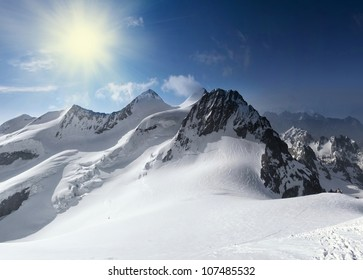 Stitched Panorama of Swiss alps with snow and sunshine