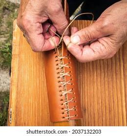 Stitching new oar leathers onto wooden oar shaft