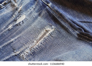 Stitching on torn denim blue jeans patched. Ripped denim jeans. Old destroy denim jeans. Denim alteration. Jeans manufacture concept.