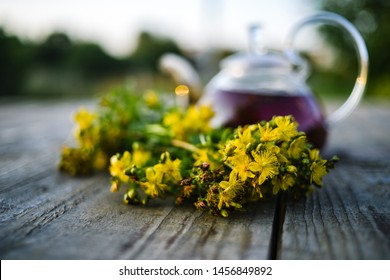 St.-John's wort bouquet, teapot blurred on the background, on wooden table.