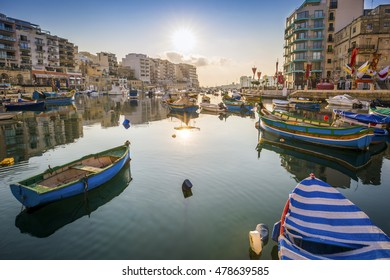St.Julian's, Malta - Sunrise at Spinola Bay with Traditional maltese Luzzu fishing boats