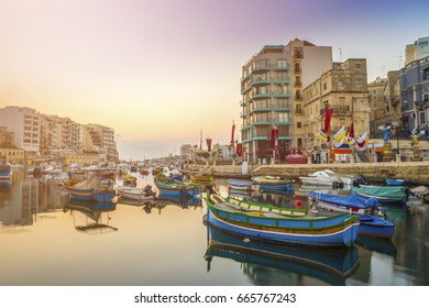 St.Julian's, Malta - Traditional colorful Luzzu fishing boats at Spinola bay at sunrise