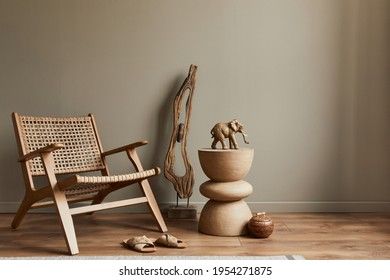 Stlish interior of living room with rattan armchair, wooden stool, elephant figure and decoration in modern home decor. Copy space. Template. - Shutterstock ID 1954271875