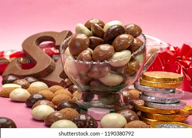 St.Nicholas day in December, children holiday in Netherlands, Belgium, Germany and Curacao, chocolate spicy ginger cookies, letters and coins on pink background copy space close up