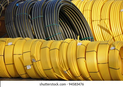 Stock black and yellow coiled plastic pipes