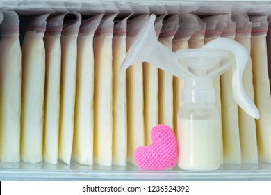 Stock of breast milk frozen in storage bags and a pump bottle for a new baby of family and pink heart with love in the freezer of refrigerator.