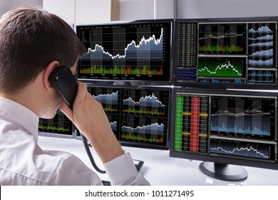 Stock Broker Talking On Telephone In Front Of Multiple Computer Screen Showing Graphs