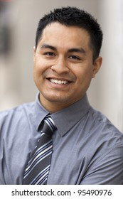 Stock closeup headshot photo of a smiling Hispanic businessman.