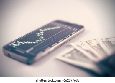 Stock exchange in blurred smartphone and wallet with dollars