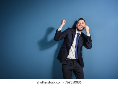 Stock exchange broker talking on phone against color background