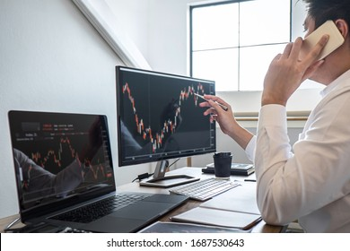 Stock exchange market concept, Business investor trading or stock brokers having a planning and analyzing with display screen and pointing on the data presented and deal on a stock exchange.