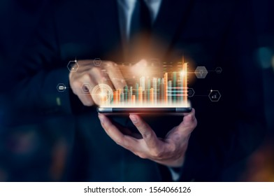 Stock exchange market concept, hand trader holding tablet with graphs analysis candle line on bokeh colors light in night.