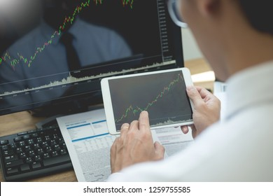 Stock exchange trader Analyzing Graphs chart or data On Multiple Screens in office