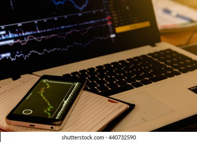 Stock graph on a mobile and notebook ( close up )