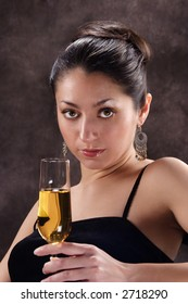 A stock image of a beautiful Latino woman holding a glass of champagne with a provocative expression. Portrait style.