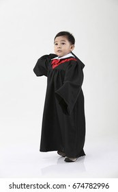 stock image of the boy wearing graduation gown about to throw his cap