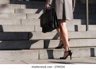 A stock image of a business woman ascending stairs holding a briefcase. Corporate. Executive.