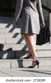 A stock image of a business woman ascending stairs holding a briefcase. Corporate. Executive. Portrait style.
