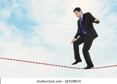 Stock image of businessman walking the tightrope