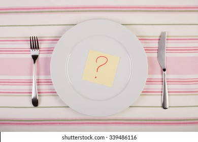 stock image of color note with question mark on white plate. diet concept