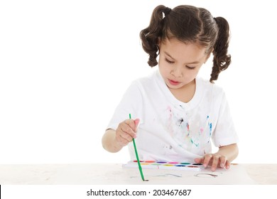 Stock image of female preschooler playing with watercolors over white background