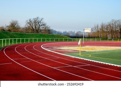 Stock image of a football field with running track in the evening, signifying concept of dreams and aspirations