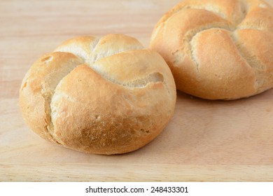 Stock image of fresh bread rolls on a chopping board