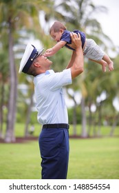 Stock image of a man raising his baby in the air