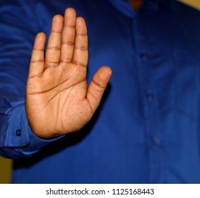 Stock image of a man wearing long sleved blue shirt, showing his palm, which indicates stop or pause