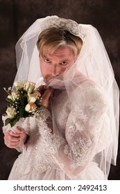 A stock image of a masculine man dressed in a bridal gown. Comical.