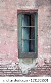 Stock image of an old window on exposed brick wall.