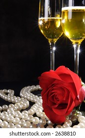 A stock image of a perfect red rose, a string of pearls and two glasses of sparkling champagne on a black background. Room for text.