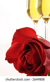 A stock image of a perfect red rose and two glasses of champagne. Champagne diffused in background. Room for text.