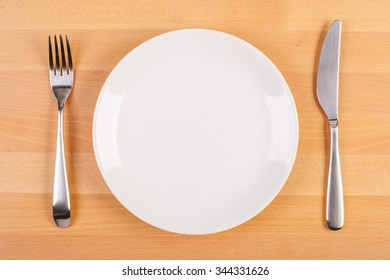 stock image of plate with knife and fork on beechwood