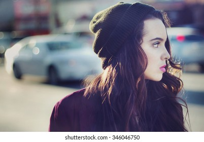 Stock image portrait of urban teen walking outdoors with a blank stare
