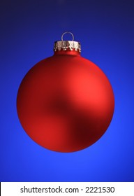 A stock image of a red Christmas ornament on a cobalt blue background.