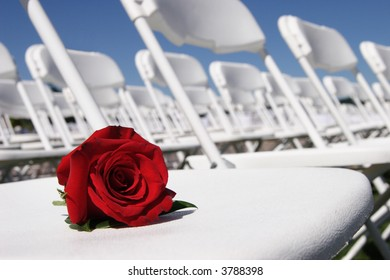 A stock image of a red rose lying on one of a sea of white chairs against a crystal blue sky.
