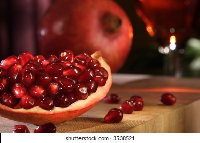 A stock image of a scene using pomegranates. Whole and seeded. Lifestyle format. Landscape.
