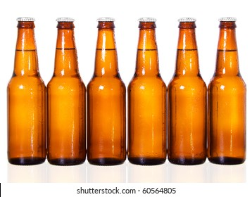 Stock image of six dark beer bottles over white background with reflection on bottom