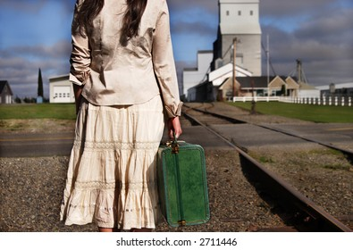 A stock image of a small town young woman holding an old suitcase and waiting for a train.