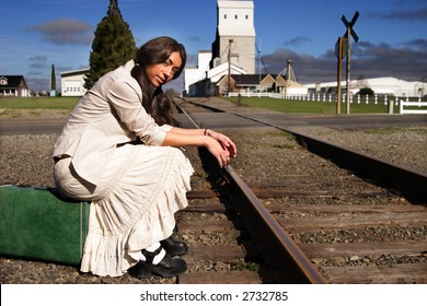A stock image of a small town young woman sitting on an old suitcase waiting for a train.