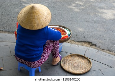 Stock image of Vietnamese vendor on the road in Hoi An old town. Women with conical hat selling street food in the morning in a small market. Hoi An old town is UNESCO world heritage