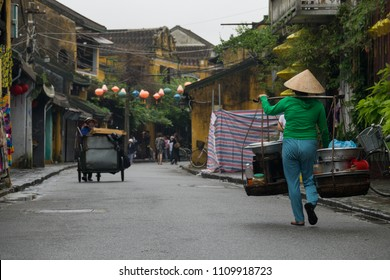 Stock image of Vietnamese woman with conical hat carries a yoke on her shoulder along the street. Women with conical hat selling street food in the morning in a small market. Hoi An old town is UNESCO