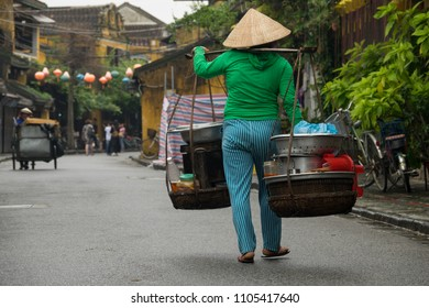 Stock image of a Vietnamese woman in national clothes and a hat carries a yoke on her shoulder along the street. Women with conical hat selling street food in the morning in a small market