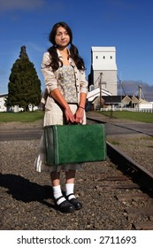 A stock image of a young woman in a rural setting waiting for a train. Suitcase. Portrait.